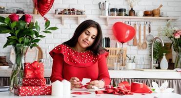 jovem escrevendo uma carta de amor sentada na cozinha decorada foto