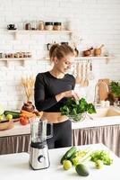 jovem loira sorridente fazendo suco de espinafre na cozinha de casa foto