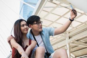 casal ama o homem e a mulher usando o smartphone para tirar uma selfie. foto