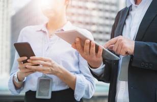 feche as mãos do empresário e da mulher usando tablet e smartphone. foto