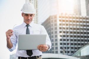 engenharia civil usando laptop enquanto trabalha na construção foto