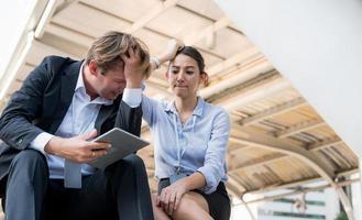 retrato de empresário e mulher olhando para um tablet e se sentindo triste foto