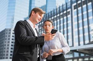 retrato de empresário e mulher olhando para o telefone foto