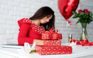 mulher segurando uma pequena caixa de presente com fita foto