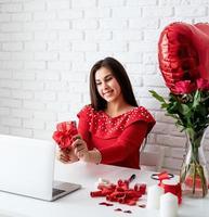 mulher namorando online segurando um presente sobre o fundo da parede de tijolos brancos foto
