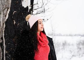 jovem em pé perto da árvore com os olhos fechados por causa da neve foto