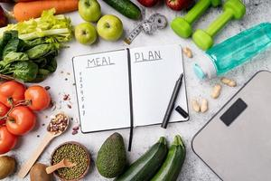 bloco de notas com palavras plano de refeições com alimentos saudáveis e equipamentos esportivos foto