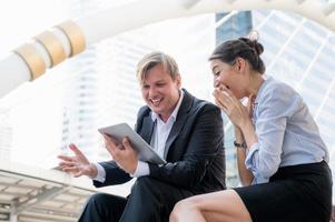 retrato de empresário e mulher olhando para o tablet foto