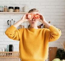 mulher engraçada brincando com tomates, fazendo salada na cozinha foto