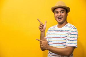 jovem asiático engraçado feliz apontando o dedo no espaço em branco foto