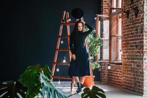 mulher de chapéu em frente a escada de madeira foto
