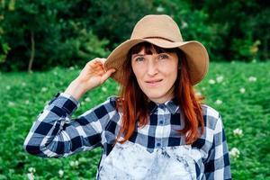 retrato mulher agricultora com um chapéu de palha na horta ao fundo foto