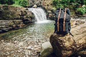 mochila de turista de alpinista hipster no fundo do rio e da cachoeira foto
