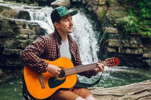homem tocando violão sentado perto de uma cachoeira foto