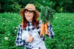 mulher segurando cenouras foto