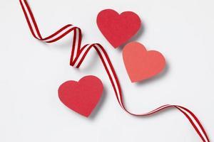 barbante listrado vermelho e branco com corações em fundo branco foto