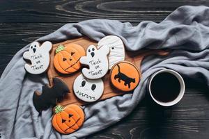 pão de mel para o halloween com uma xícara de café em um fundo preto. foto