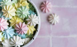 pequenos merengues coloridos no prato de cerâmica foto