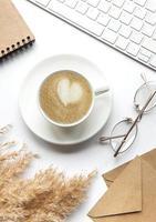 mesa de escritório área de trabalho com notebook, café e grama de pampa. foto