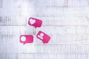 papel cortado ícones de mídia social em fundo de madeira foto