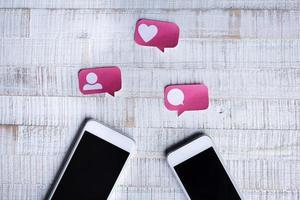 ícones de mídia social de corte de papel com conteúdo para dois smartphones foto