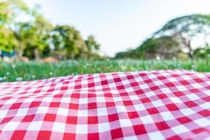 textura de toalha de mesa quadriculada vermelha com grama verde no jardim foto