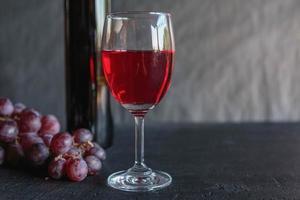 vinho tinto e garrafa de vinho com uvas em fundo preto foto