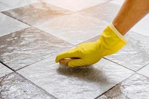 usando um limpador de piso de madeira para esfregar o piso de ladrilho. foto