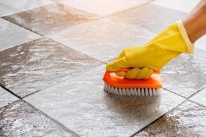 usando um limpador de piso de plástico para esfregar o piso de ladrilho. foto