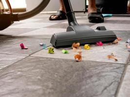 varra pedaços de papel e poeira do piso de cerâmica com um aspirador de pó. foto