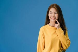 jovem asiática mostrando um sorriso, uma expressão positiva sobre fundo azul. foto