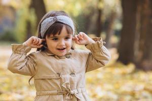 linda garota fecha os ouvidos com os dedos no parque de outono foto