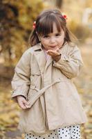 linda garotinha mostra um beijo no ar no parque de outono foto