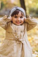 a garota fecha os ouvidos com os dedos no parque de outono. foto