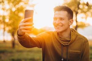 cara segurando um buquê de folhas e tirando uma selfie no parque foto