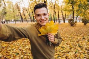 o cara segurando um buquê de folhas de outono e tirando uma selfie no parque foto