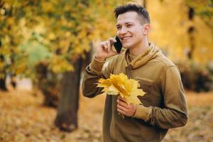 cara feliz sorrindo e falando ao telefone no parque de outono foto