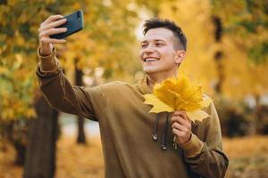 cara sorrindo e segurando um buquê de folhas e tirando uma selfie no parque foto