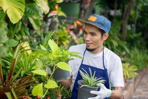 homem asiático feliz vende jardim de plantas na loja foto