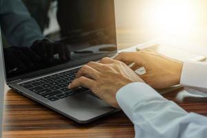 computador de digitação à mão no espaço de trabalho do escritório foto