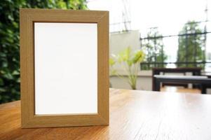 simulação de moldura em branco em pé na mesa de madeira foto