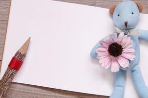 lápis de madeira esboço em branco papel branco boneca urso azul flor roxa foto