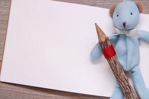 lápis de madeira desenho em branco papel branco boneca urso azul foto