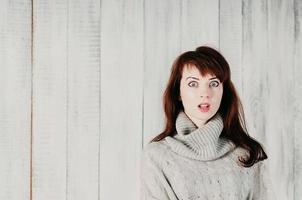 mulher chocada em fundo branco de madeira foto