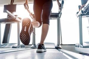 parte inferior do corpo na parte das pernas da garota fitness na esteira foto