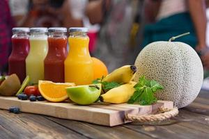 frutas frescas e garrafa de suco na mesa foto