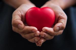 feche as mãos dando um coração vermelho como doador de coração foto