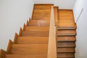 escada, piso de madeira e corrimão de ferro preto. foto