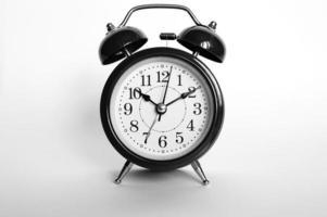despertador analógico redondo preto isolado no fundo branco. tempo 1010. pintado de preto cinza foto
