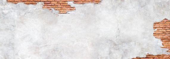 parede de tijolos antigos sob gesso danificado foto